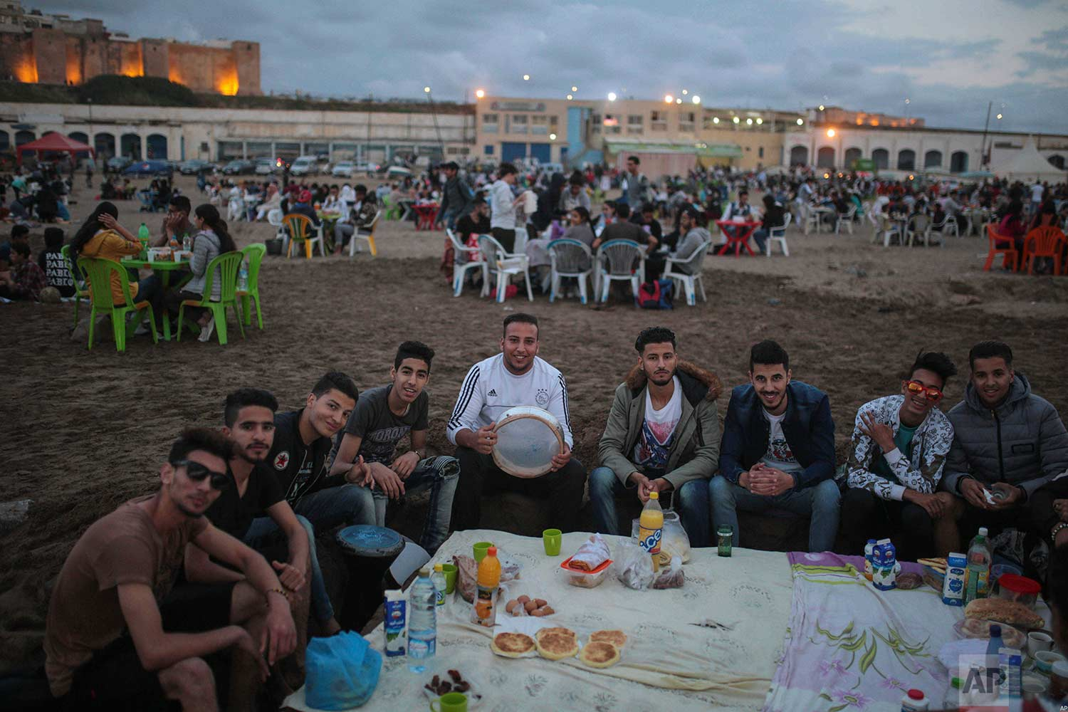 Young men pose for a photo as they gather to break their fast on the beach in the holy month of Ramadan, in Rabat, Morocco, Saturday, June 9, 2018. (AP Photo/Mosa'ab Elshamy)