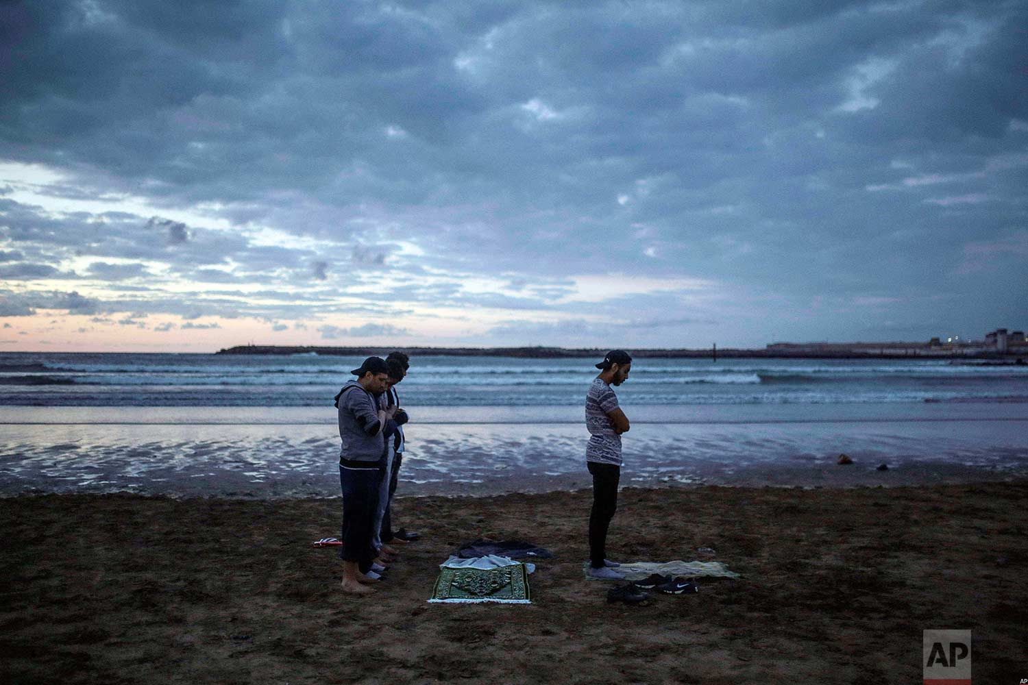 Men pray sunset prayers after breaking their fast on the beach in the holy month of Ramadan, Rabat, Morocco, Saturday, June 9, 2018. (AP Photo/Mosa'ab Elshamy)
