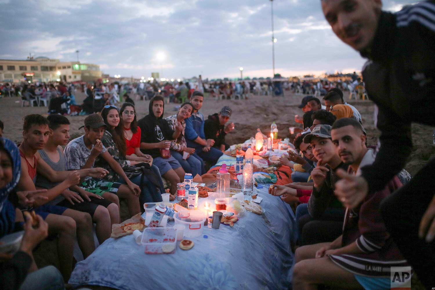 Friends pose for a photo as they prepare to break their fast on the beach, in the holy month of Ramadan, Rabat, Morocco, Saturday, June 9, 2018. (AP Photo/Mosa'ab Elshamy)