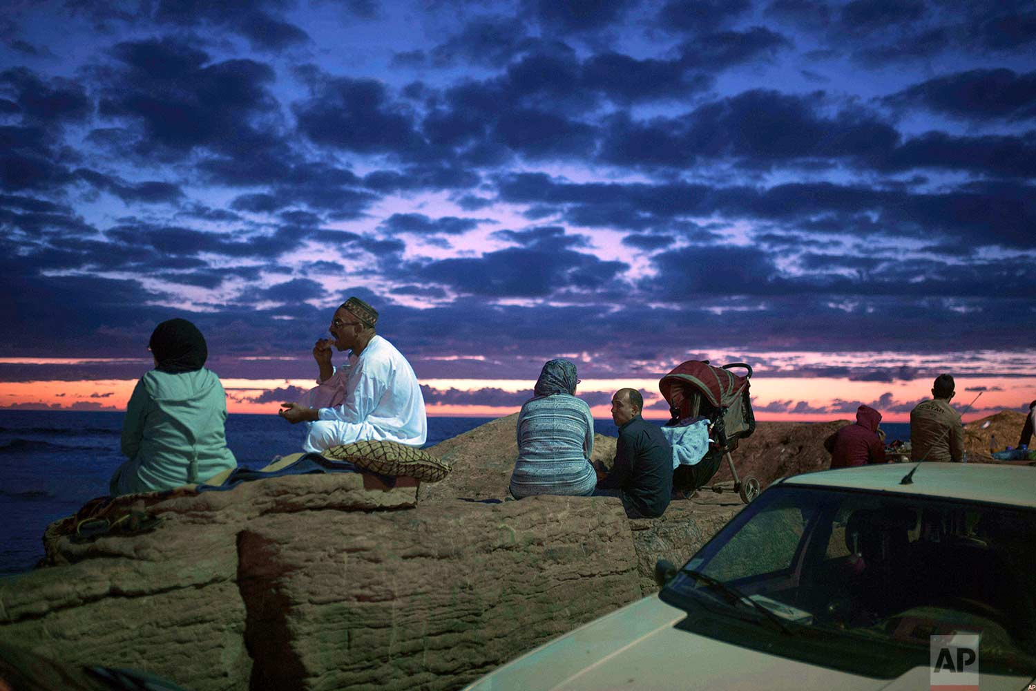 Couples observe the sunset as they break their fast on the beach in the holy month of Ramadan, Rabat, Morocco, Saturday, June 9, 2018. (AP Photo/Mosa'ab Elshamy)