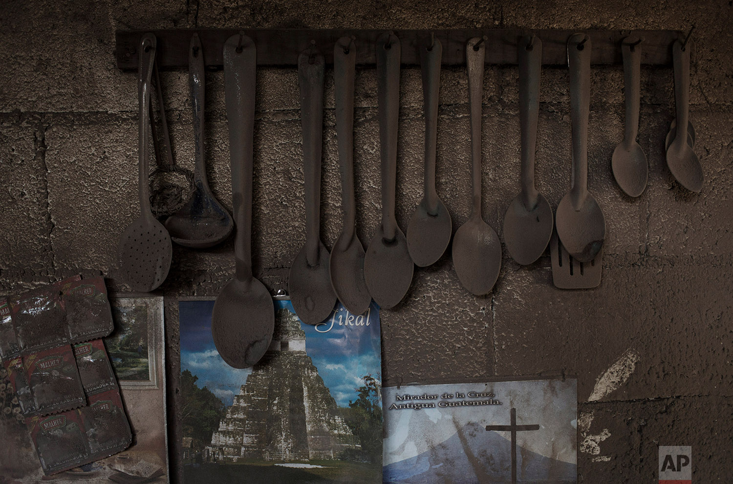 This June 9, 2018 photo shows kitchen utensils hanging above posters promoting the Mayan ruins Tikal and the Mirador de la Cruz, dusted with volcanic ash spewed by the Volcan de Fuego or Volcano of Fire, in San Miguel Los Lotes, Guatemala. (AP Photo/Rodrigo Abd)