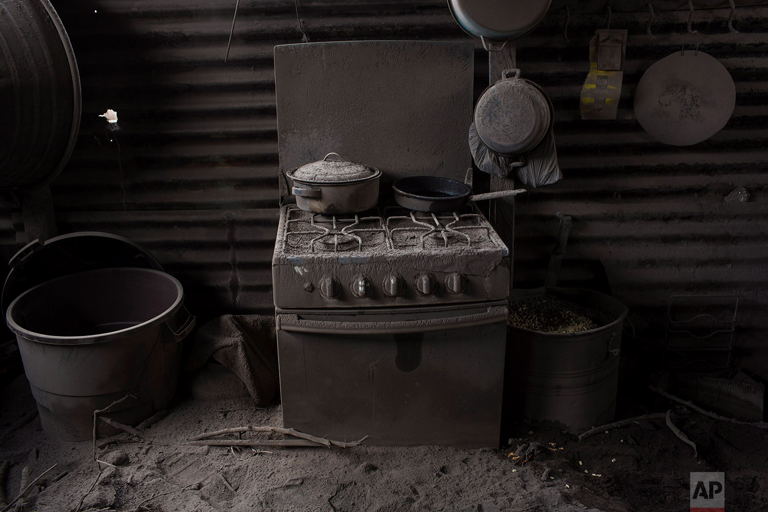 This June 11, 2018 photo shows a kitchen blanketed in volcanic ash spewed by the Volcan de Fuego or Volcano of Fire, in San Miguel Los Lotes, Guatemala. (AP Photo/Rodrigo Abd)