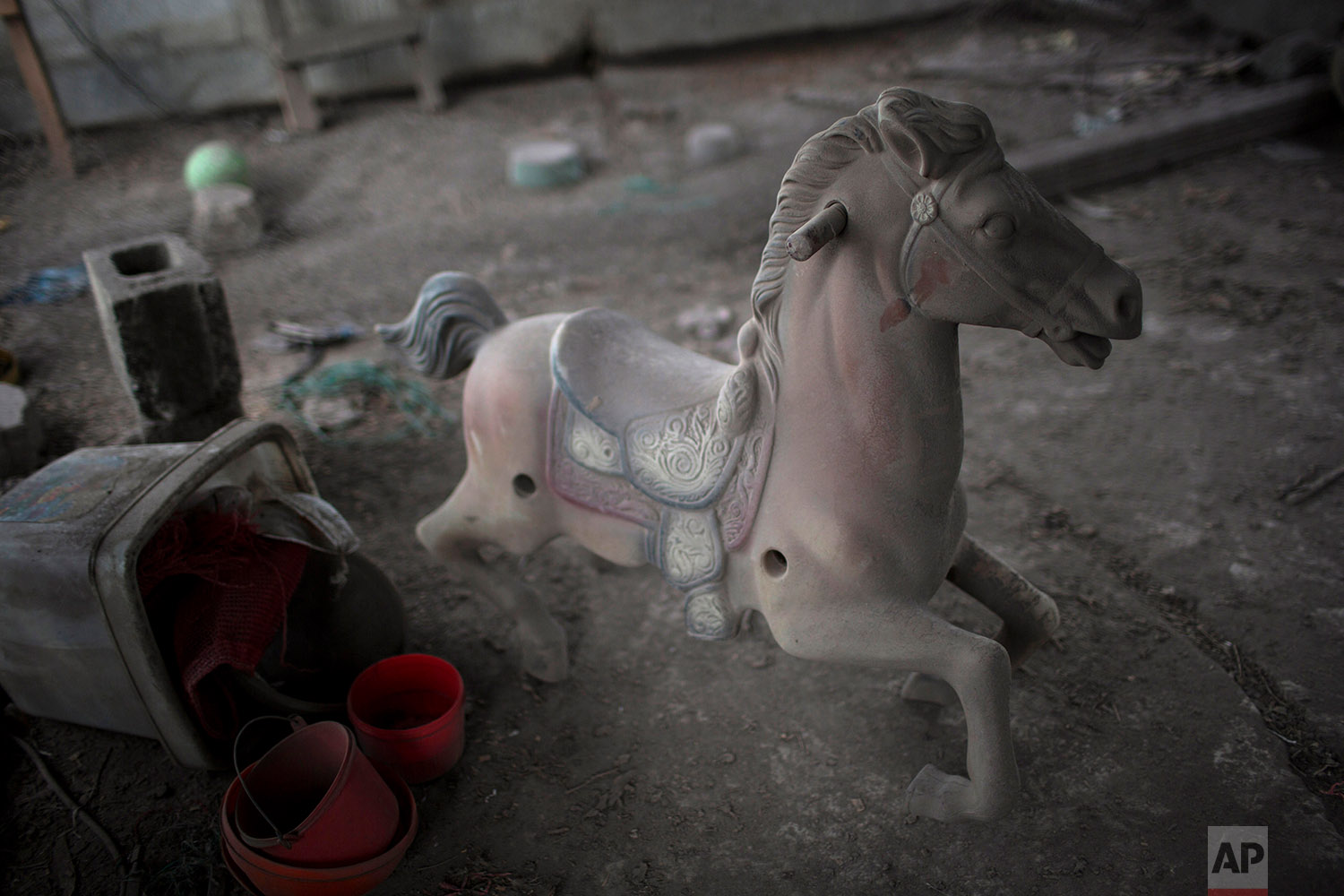 This June 8, 2018 photo shows a spring pony dusted with volcanic ash spewed by the Volcan de Fuego or Volcano of Fire, on the balcony of a home in San Miguel Los Lotes, Guatemala. (AP Photo/Rodrigo Abd)