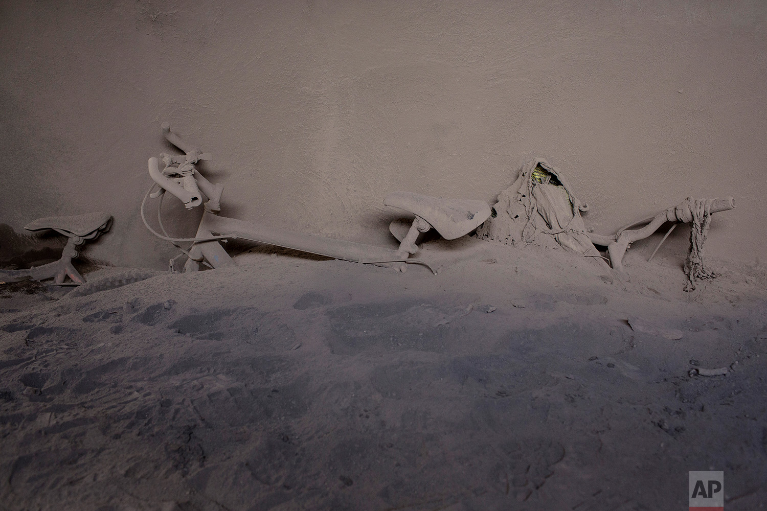 This June 9, 2018 photo shows bicycles leaning against a wall in the entry hall of a home entombed with volcanic ash spewed by the Volcan de Fuego or Volcano of Fire, in San Miguel Los Lotes, Guatemala. (AP Photo/Rodrigo Abd)