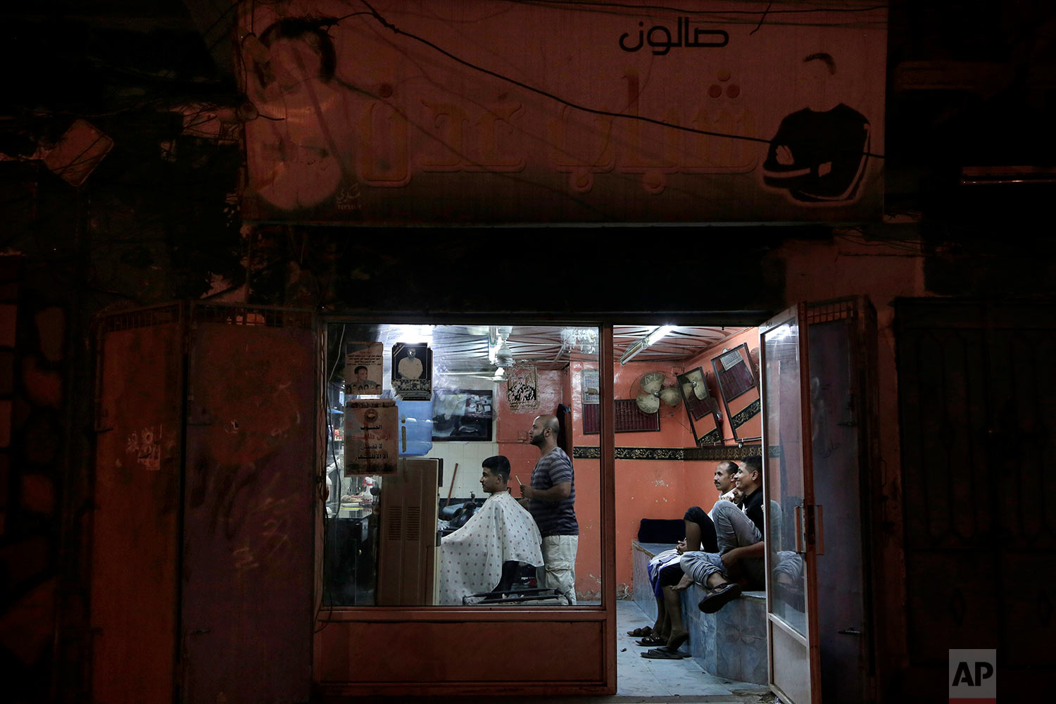 18-year-old Abdullah gets his hair cut at a barbershop in Aden, Yemen. (AP Photo/Nariman El-Mofty)
