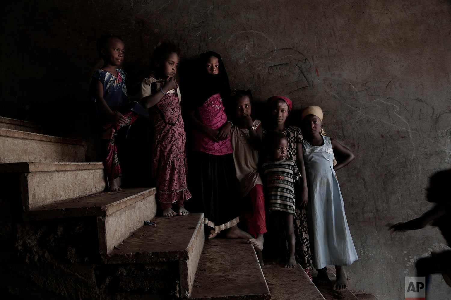 Displaced girls pose for a photograph inside a school turned into a camp for displaced persons in Khanfar, Abyan, Yemen. (AP Photo/Nariman El-Mofty)
