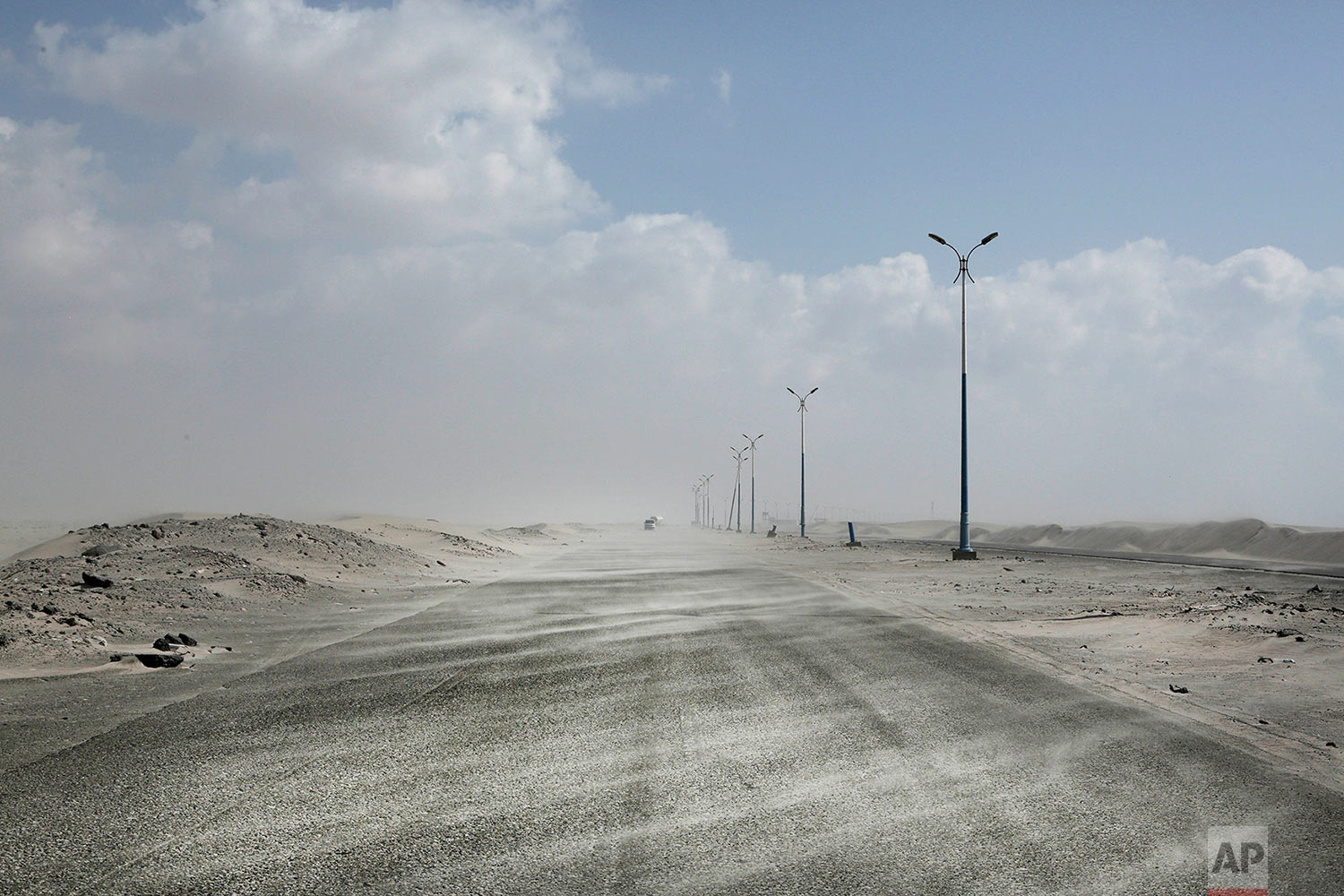 Sand drifting over an empty highway from Abyan to Aden in Yemen. (AP Photo/Nariman El-Mofty)
