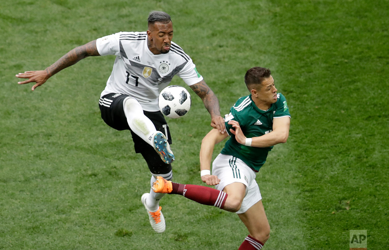 Germany's Jerome Boateng, left, and Mexico's Javier Hernandez challenge for the ball during the group F match between Germany and Mexico at the 2018 soccer World Cup in the Luzhniki Stadium in Moscow, Russia, Sunday, June 17, 2018. (AP Photo/Michael Probst)