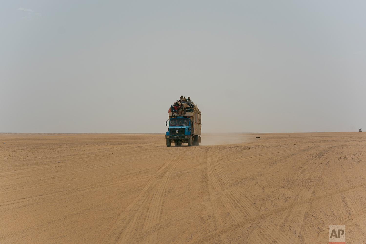 A truck carrying goods and migrants drives through Niger's Tenere desert region of the south central Sahara on Sunday, June 3, 2018. Once a well-worn roadway for overlander tourists, the highway's 4,500 kilometers (2,800 miles) are a favored path for migrants heading north in hopes of a better life -and more recently thousands who are being expelled south from Algeria. (AP Photo/Jerome Delay)