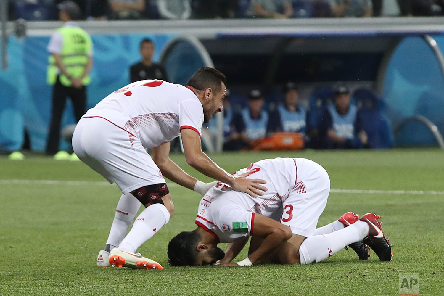 Tunisia's Ferjani Sassi, right, kisses the pitch as he celebrates after scoring during the group G match between Tunisia and England at the 2018 soccer World Cup in the Volgograd Arena in Volgograd, Russia, Monday, June 18, 2018. (AP Photo/Thanassis Stavrakis)