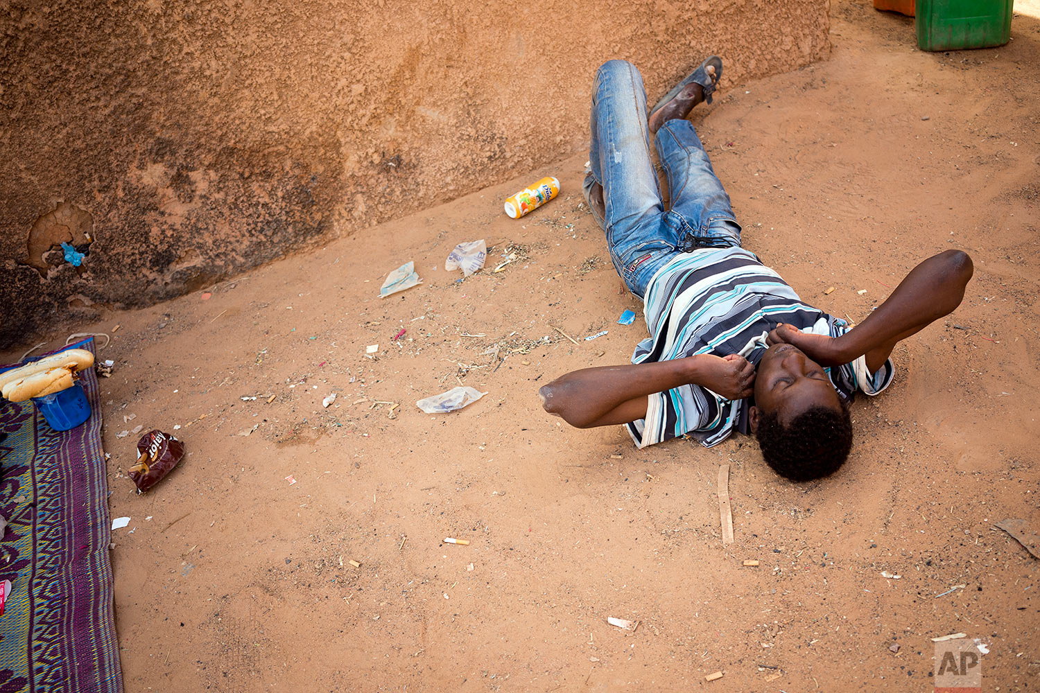 A young migrant who has been expelled from Algeria lays after being restrained by others after he attempted to strip naked in a transit center in Arlit, Niger, on June 2, 2018. (AP Photo/Jerome Delay)