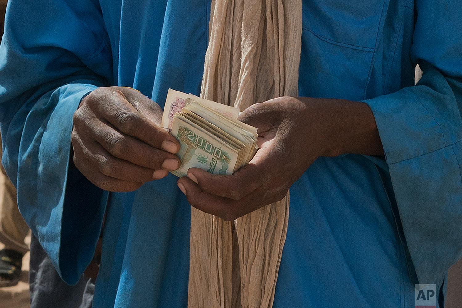 A smuggler counts his money as migrants climb into trucks to head north into Algeria at the Assamaka border post in northern Niger on Sunday, June 3, 2018. (AP Photo/Jerome Delay)