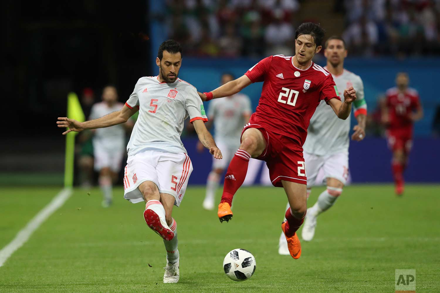 Spain's Sergio Busquets, left, fights for the ball with Iran's Sardar Azmoun during the group B match between Iran and Spain at the 2018 soccer World Cup in the Kazan Arena in Kazan, Russia, Wednesday, June 20, 2018. (AP Photo/Thanassis Stavrakis)