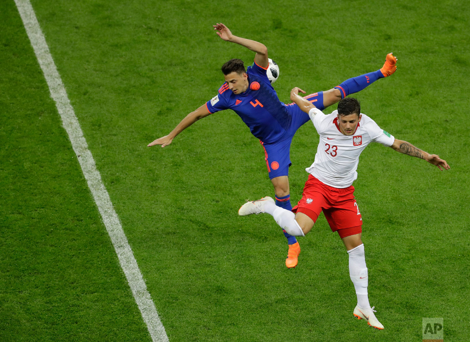 Colombia's Santiago Arias, left, and Poland's Dawid Kownacki battle for the ball during the group H match between Poland and Colombia at the 2018 soccer World Cup at the Kazan Arena in Kazan, Russia, Sunday, June 24, 2018. (AP Photo/Sergei Grits)