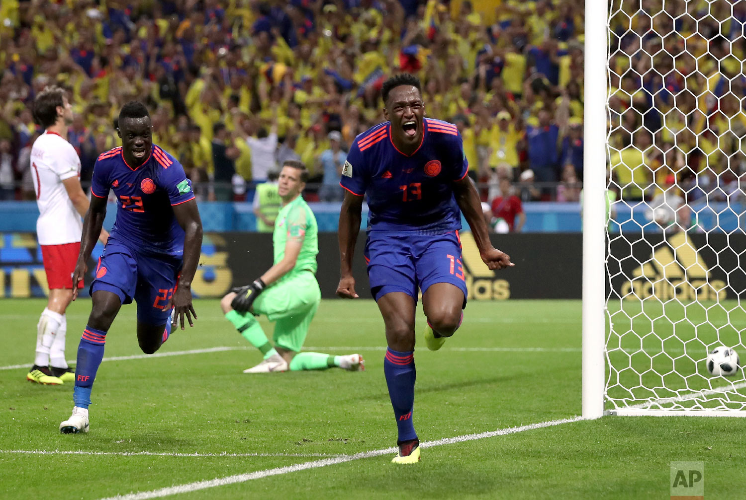 Colombia's scorer Yerry Mina, right and his teammate Davinson Sanchez, left, celebrate the opening goal during the group H match between Poland and Colombia at the 2018 soccer World Cup at the Kazan Arena in Kazan, Russia, Sunday, June 24, 2018. (AP Photo/Thanassis Stavrakis)