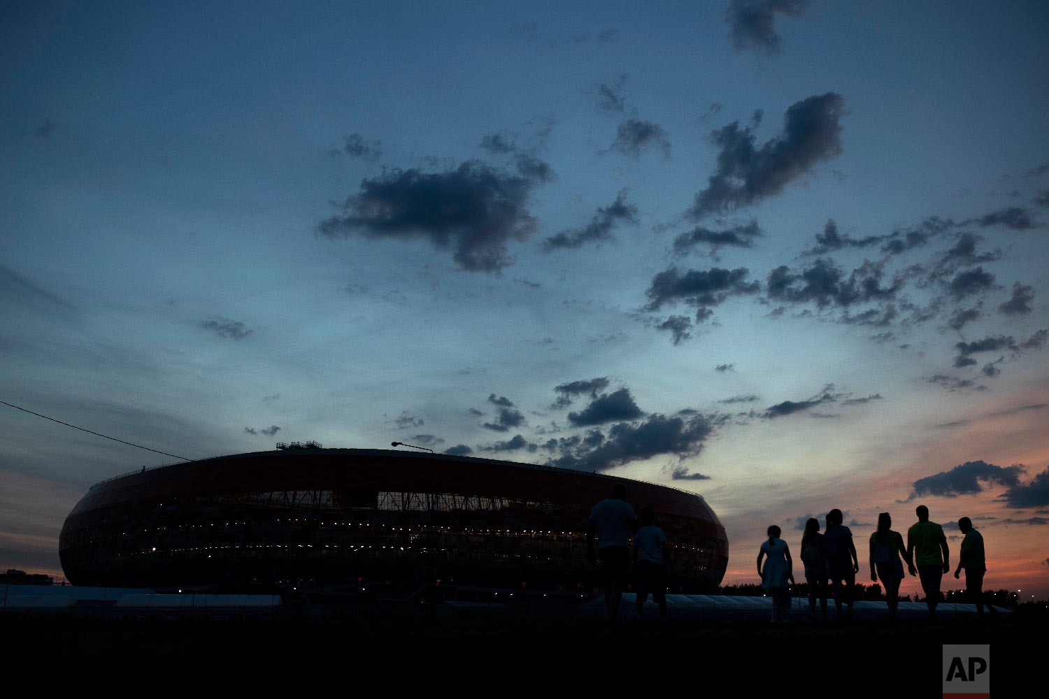 People walk next to the Mordovia Arena stadium as the sun sets at the 2018 soccer World Cup in Saransk, Russia on June 24, 2018. (AP Photo/Francisco Seco)