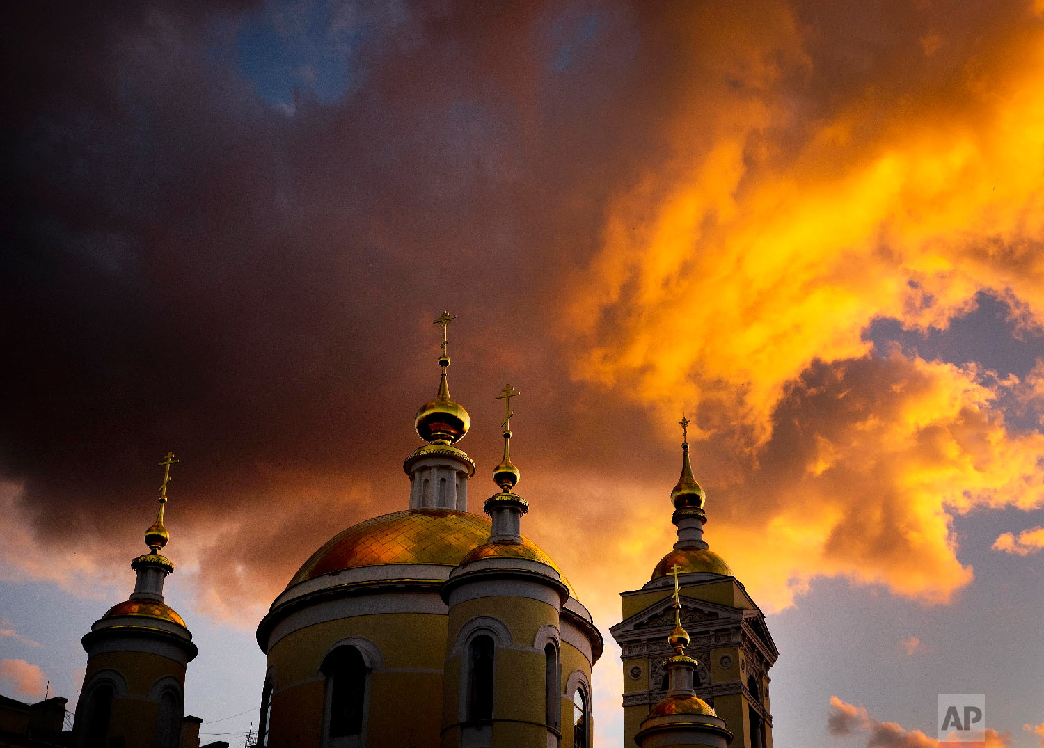 Clouds are illuminated by the sun setting sun over a church during the 2018 soccer World Cup in Podolsk near Moscow, Russia on June 19, 2018. (AP Photo/Michael Probst)