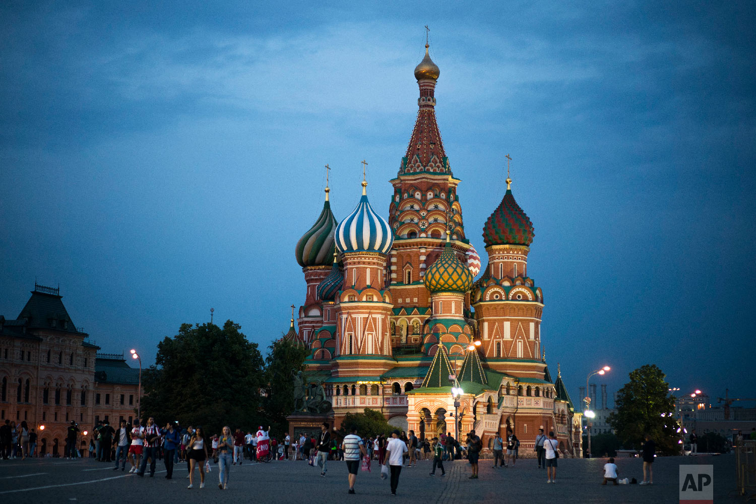 Tourists walk near the Saint Basil's Cathedral at dusk during the 2018 soccer World Cup in Moscow, Russia on June 19, 2018. (AP Photo/Felipe Dana)