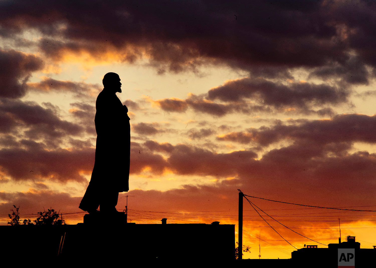 A Lenin statue stands on a column as the sun sets during the 2018 soccer World Cup in Podolsk near Moscow, Russia on June 21, 2018. (AP Photo/Michael Probst)