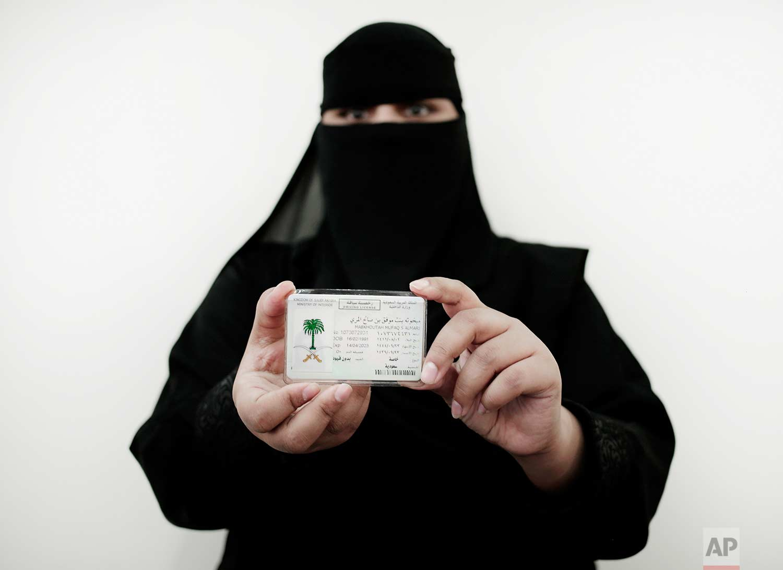In this June 23, 2018 photo, 27-year old Mabkhoutah al-Mari poses for a photograph holding her new car license at the Saudi Driving School inside Princess Nora University in Saudi Arabia. (AP Photo/Nariman El-Mofty)