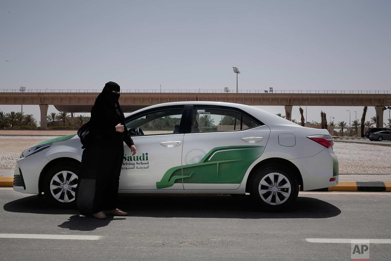 In this June 23, 2018 photo, 27-year old driving instructor Mabkhoutah al-Mari stands next to a test drivers car at the Saudi Driving School inside Princess Nora University in Saudi Arabia.(AP Photo/Nariman El-Mofty)