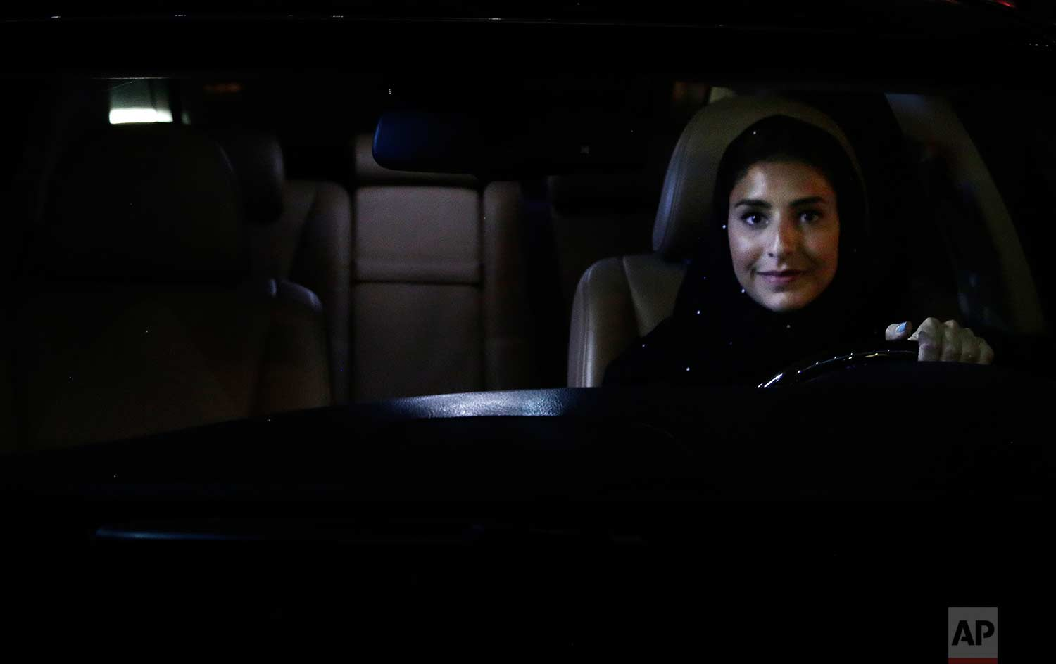 Hessah al-Ajaji sits in her car on the capital's busy Tahlia Street after driving for the first time in Riyadh, Saudi Arabia, Sunday, June 24, 2018. Saudi women are in the driver's seat for the first time in their country and steering their way through busy city streets just minutes after the world's last remaining ban on women driving was lifted on Sunday. (AP Photo/Nariman El-Mofty)