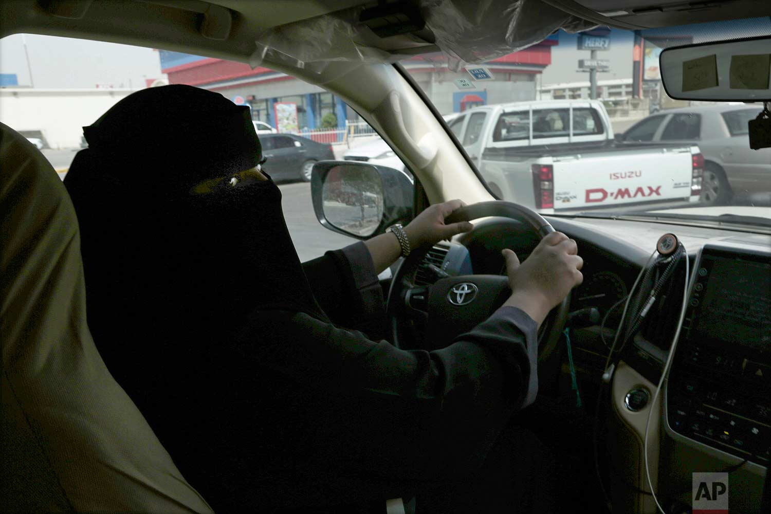 """Mabkhoutah al-Mari drives to work for the first time in Riyadh, Saudi Arabia, Sunday, June 24, 2018. """"It feels beautiful. It was a dream for us so when it happens in reality, I am between belief and disbelief -- between a feeling of joy and astonishment,"""" said Mari as she pulled up to order a drive-thru coffee on her way to work. (AP Photo/Nariman El-Mofty)"""