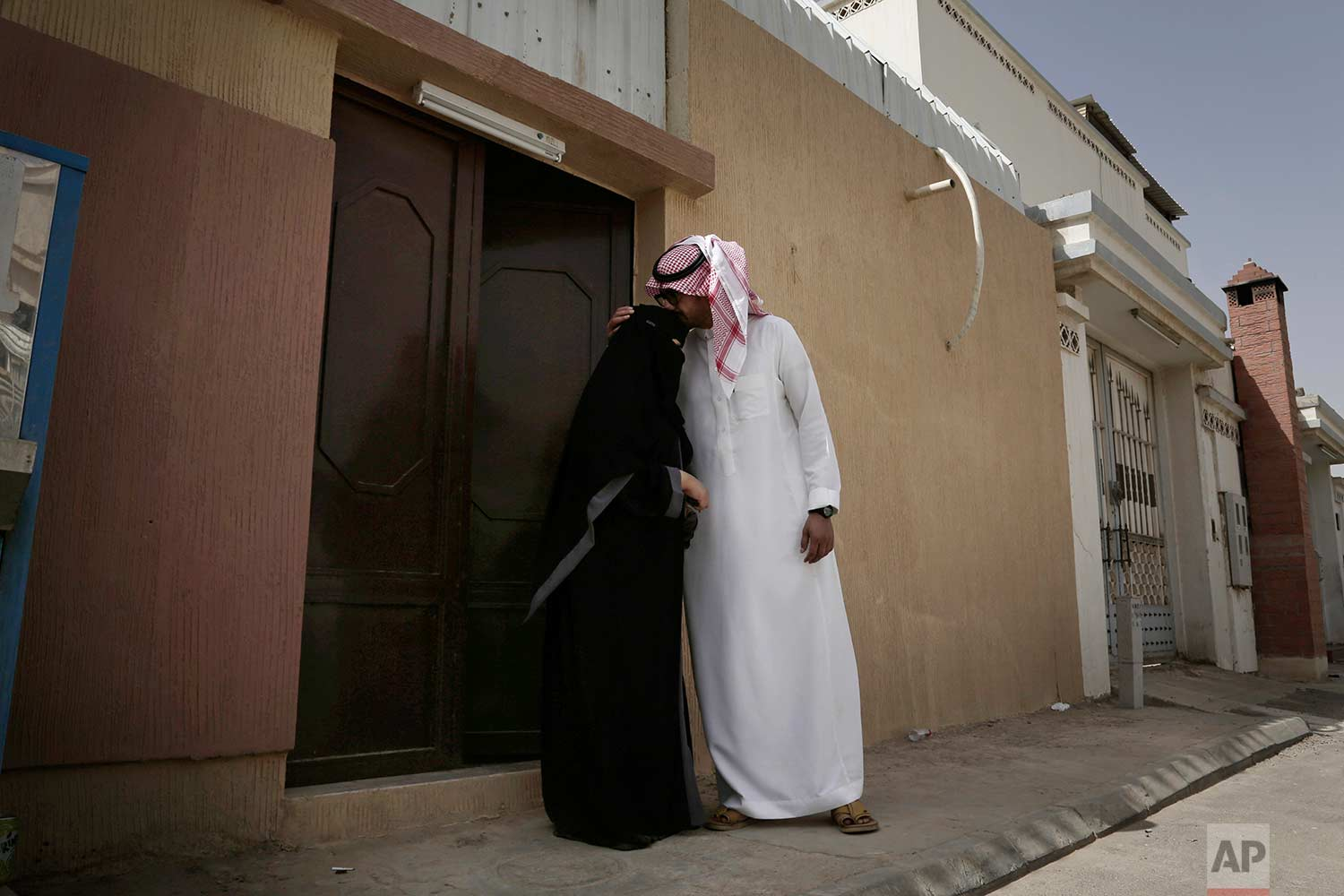 In this Sunday, June 24, 2018 photo, the brother of 27-year old Mabkhoutah al-Mari, kisses her forehead before she drives to work for the first time in Riyadh, Saudi Arabia. (AP Photo/Nariman El-Mofty)
