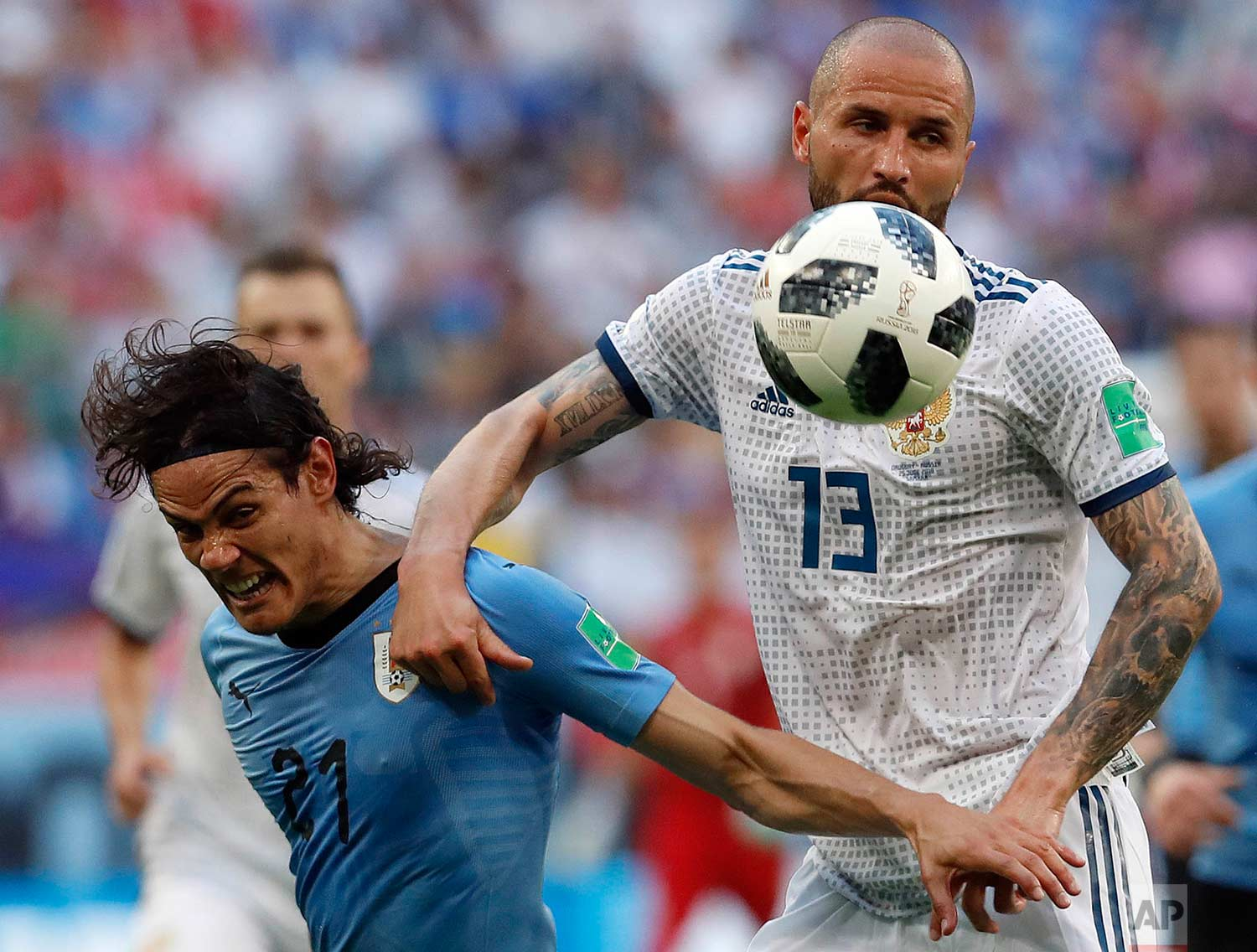 Uruguay's Edinson Cavani, left, and Russia's Fyodor Kudryashov challenge for the ball during the group A match between Uruguay and Russia at the 2018 soccer World Cup at the Samara Arena in Samara, Russia, Monday, June 25, 2018. (AP Photo/Hassan Ammar)