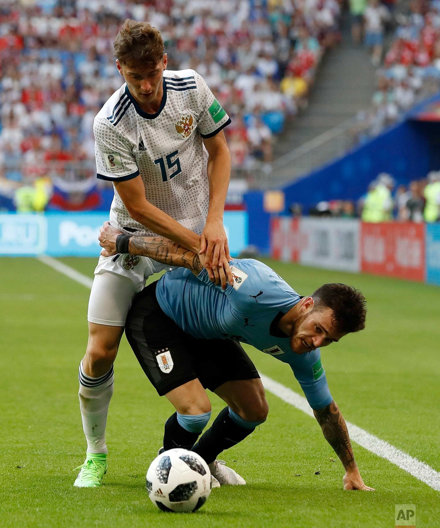 Russia's Alexei Miranchuk, left, stops Uruguay's Nahitan Nandez during the group A match between Uruguay and Russia at the 2018 soccer World Cup at the Samara Arena in Samara, Russia, Monday, June 25, 2018. (AP Photo/Rebecca Blackwell)