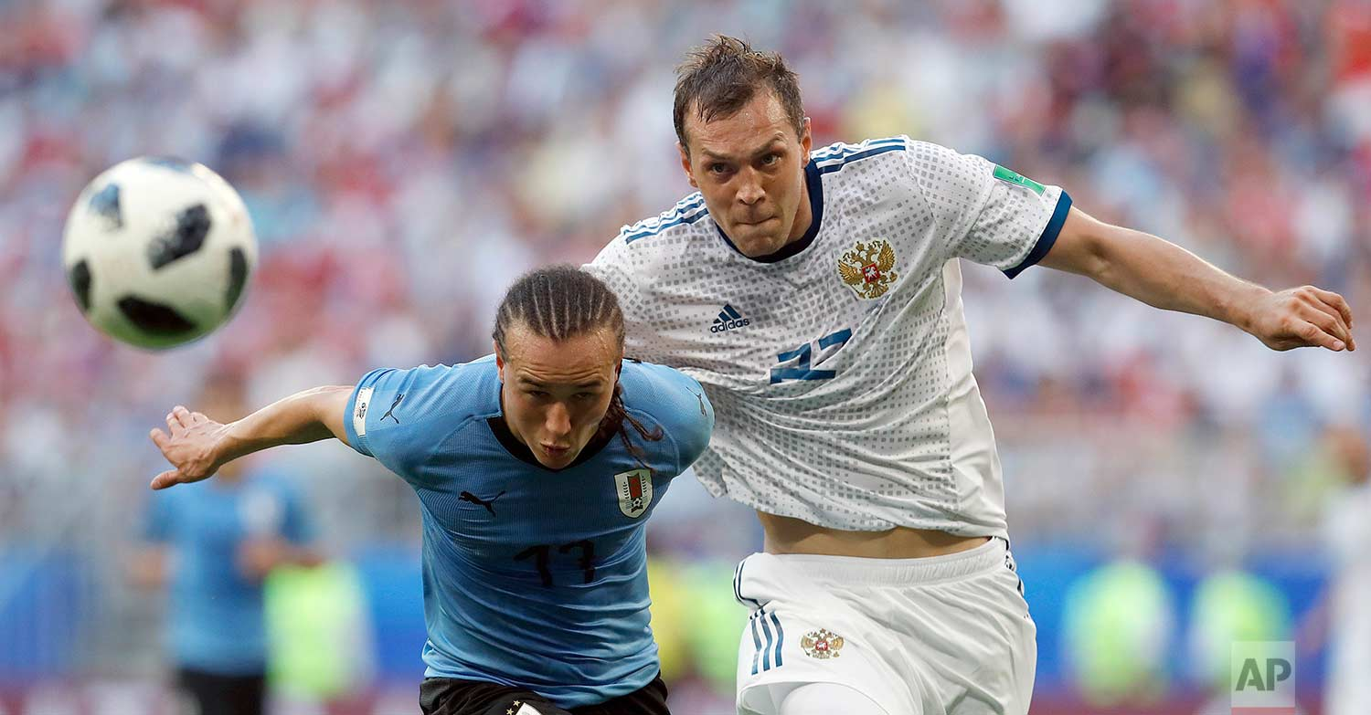 Uruguay's Diego Laxalt, left, and Russia's Artyom Dzyuba challenge for the ball during the group A match between Uruguay and Russia at the 2018 soccer World Cup at the Samara Arena in Samara, Russia, Monday, June 25, 2018. (AP Photo/Hassan Ammar)