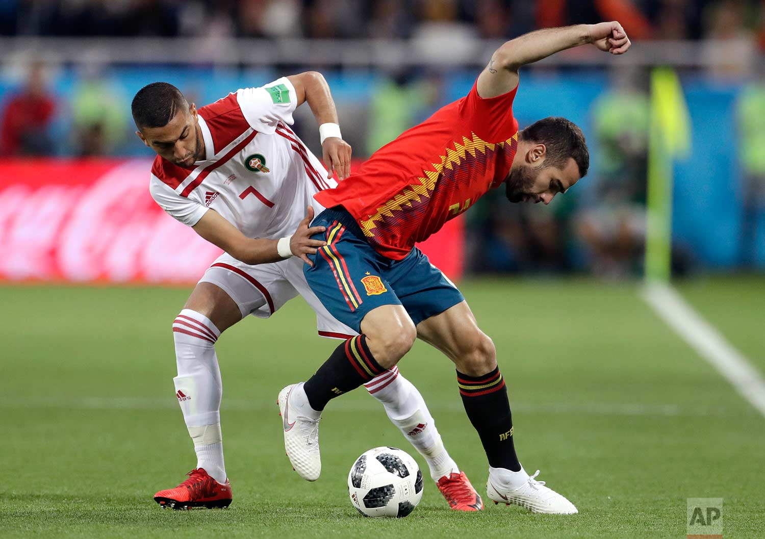 Morocco's Hakim Ziyach, left, challenges for the ball with Spain's Dani Carvajal during the group B match between Spain and Morocco at the 2018 soccer World Cup at the Kaliningrad Stadium in Kaliningrad, Russia, Monday, June 25, 2018. (AP Photo/Petr David Josek)