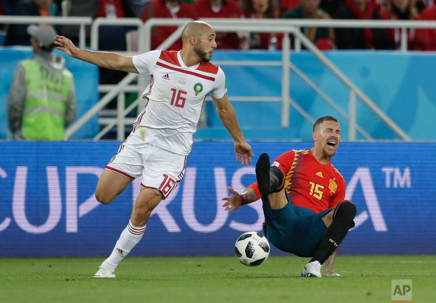 Spain's Sergio Ramos, right falls, loosing his shoe after a tackle by Morocco's Noureddine Amrabat, left, during the group B match between Spain and Morocco at the 2018 soccer World Cup at the Kaliningrad Stadium in Kaliningrad, Russia, Monday, June 25, 2018. (AP Photo/Petr David Josek)