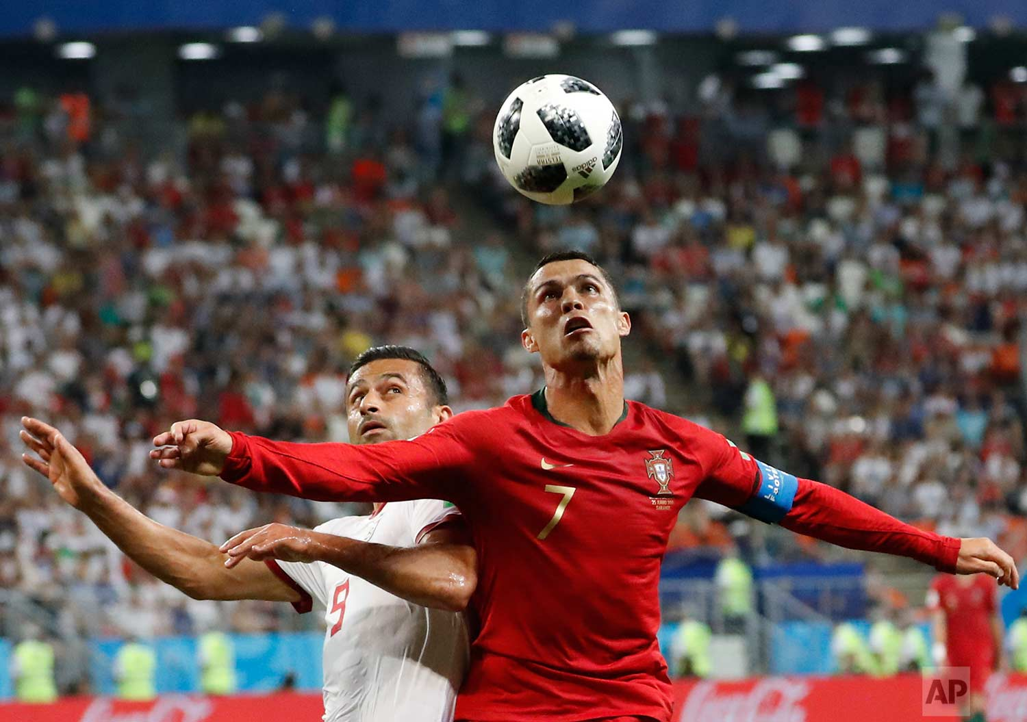Portugal's Cristiano Ronaldo, right, and Iran's Omid Ebrahimi challenge for the ball during the group B match between Iran and Portugal at the 2018 soccer World Cup at the Mordovia Arena in Saransk, Russia, Monday, June 25, 2018. (AP Photo/Pavel Golovkin)