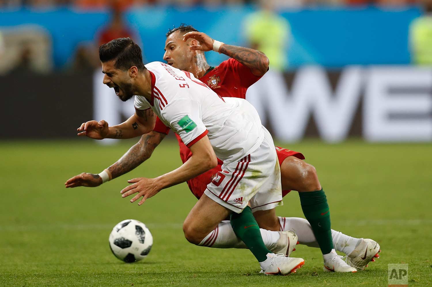 Iran's Saeid Ezatolahi front, falls as he is tackled by Portugal's Ricardo Quaresma during the group B match between Iran and Portugal at the 2018 soccer World Cup at the Mordovia Arena in Saransk, Russia, Monday, June 25, 2018. (AP Photo/Francisco Seco)