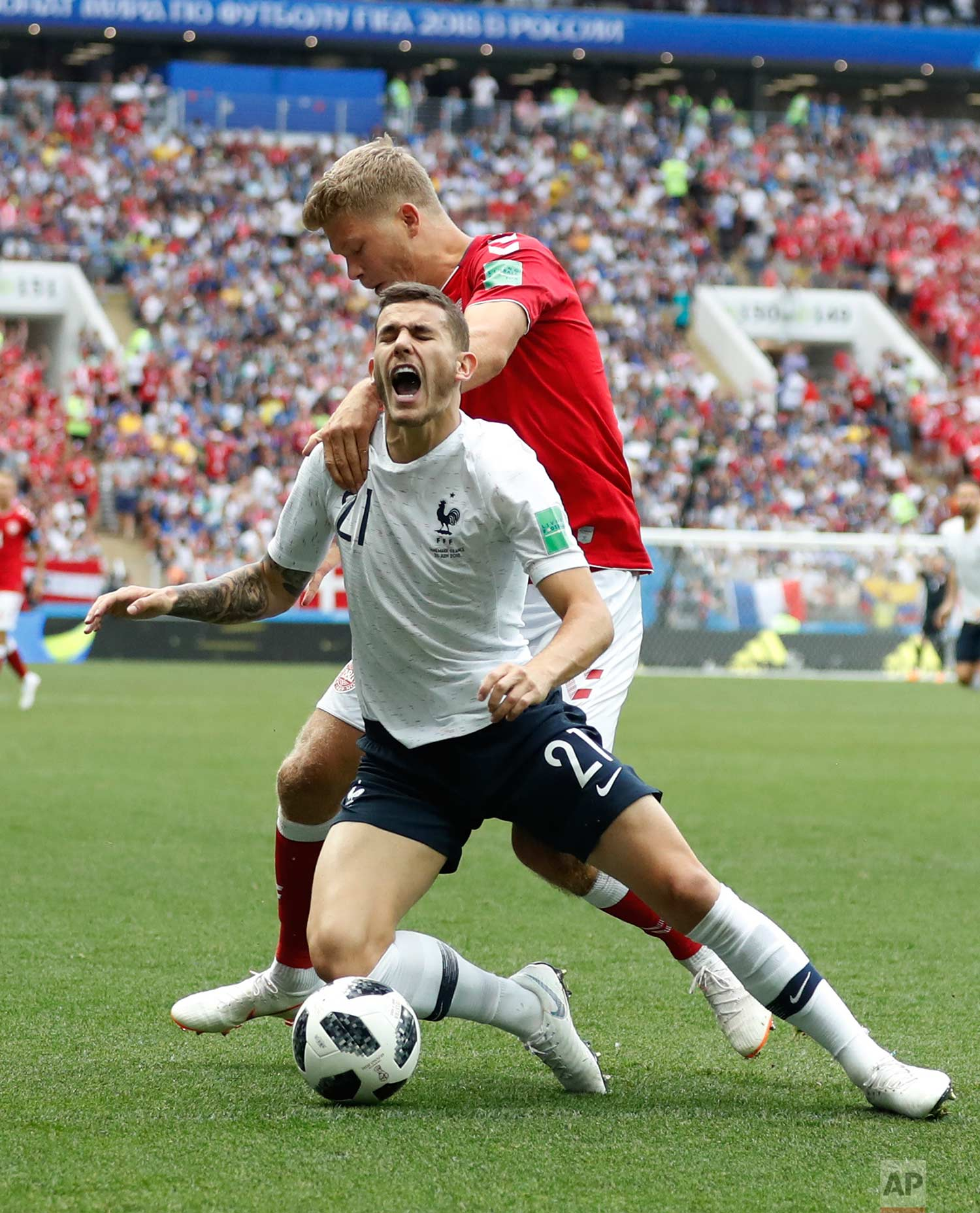 Denmark's Andreas Cornelius, top, vies for the ball with France's Lucas Hernandez during the group C match between Denmark and France at the 2018 soccer World Cup at the Luzhniki Stadium in Moscow, Russia, Tuesday, June 26, 2018. (AP Photo/Antonio Calanni)