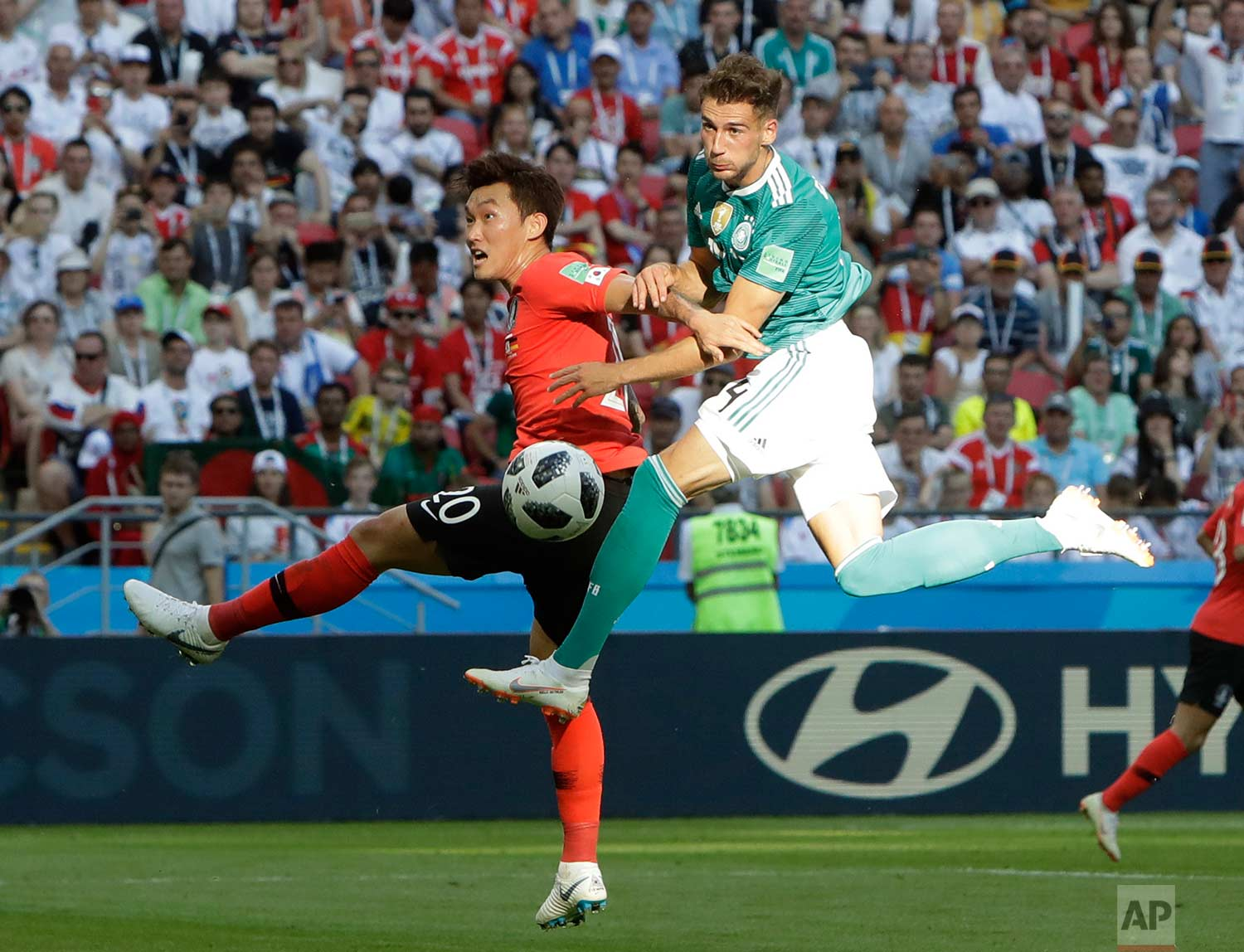 Germany's Leon Goretzka, right, and South Korea's Jang Hyun-soo challenge for the ball during the group F match between South Korea and Germany, at the 2018 soccer World Cup in the Kazan Arena in Kazan, Russia, Wednesday, June 27, 2018. (AP Photo/Michael Probst)