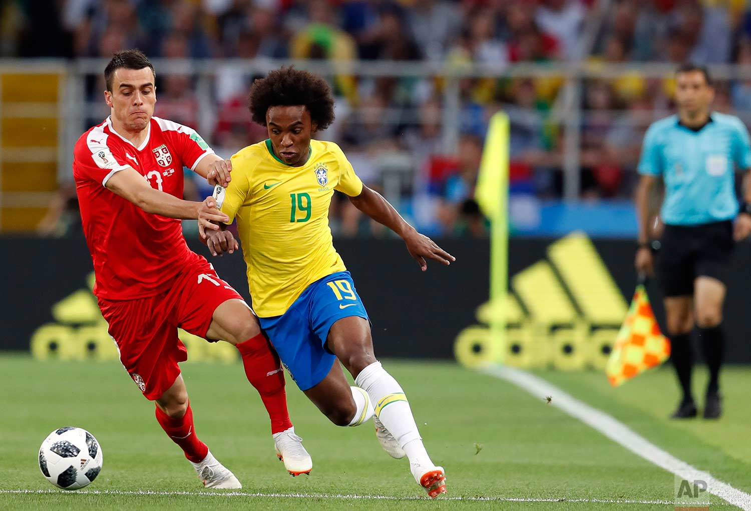 Brazil's Willian, right, is challenged by Serbia's Filip Kostic during the group E match between Serbia and Brazil, at the 2018 soccer World Cup in the Spartak Stadium in Moscow, Russia, Wednesday, June 27, 2018. (AP Photo/Rebecca Blackwell)