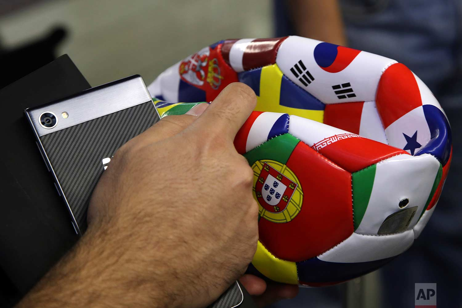 In this Saturday, June 16, 2018 photo, a supporter of Portugal holds a ball he bought at an airport shop at Sochi International Airport in Sochi, Russia. (AP Photo/Thanassis Stavrakis)