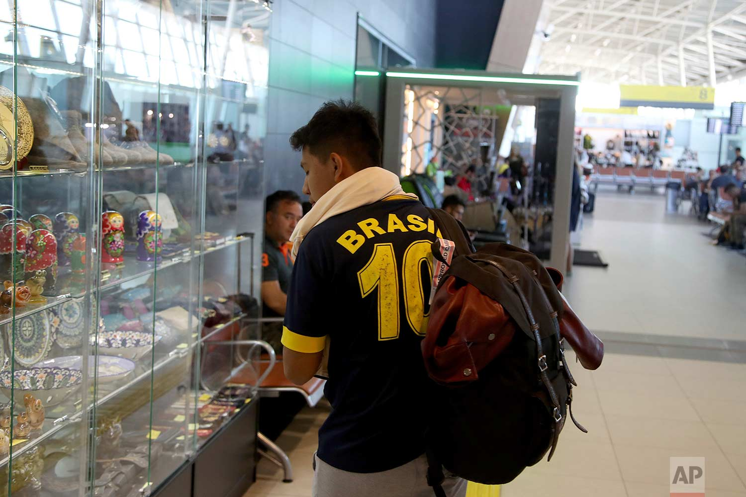 In this Friday, June 22, 2018 photo, a supporter of Brazil looks at souvenirs on sale at the Kazan International Airport in Kazan, Russia. (AP Photo/Thanassis Stavrakis)