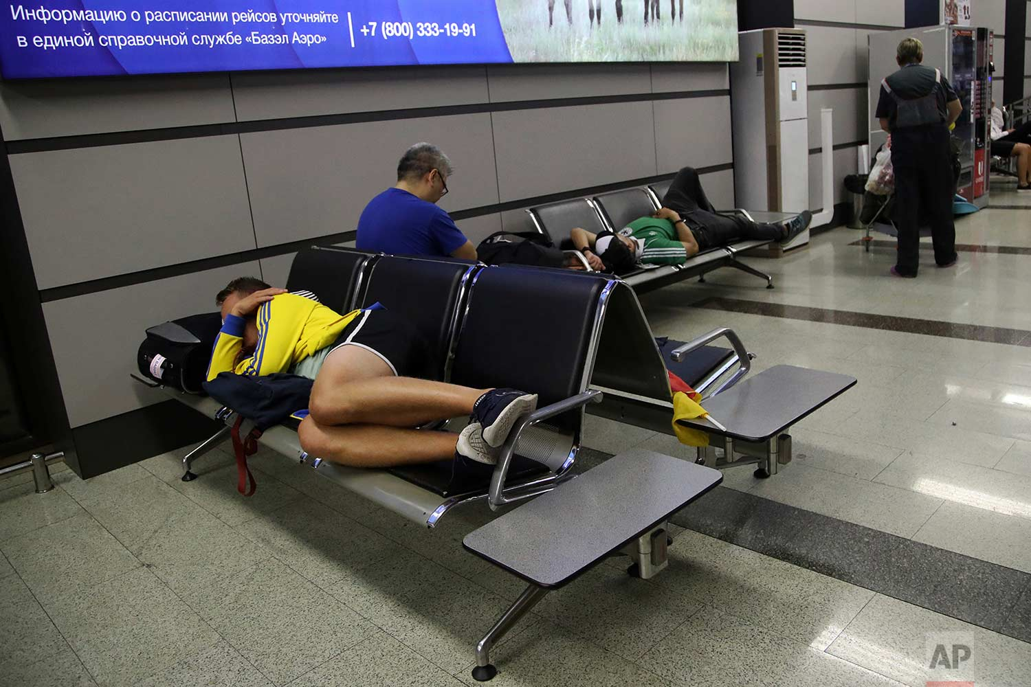 In this Sunday, June 24, 2018 photo, supporters of Sweden and Germany sleep before their flight at the Sochi International Airport in Sochi, Russia.  (AP Photo/Thanassis Stavrakis)
