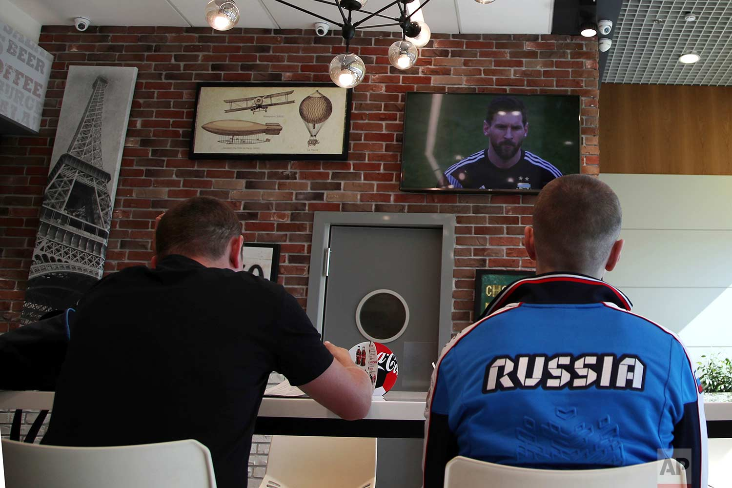 In this Saturday, June 16, 2018 photo, the TV shows the soccer star Lionel Messi during a match between Argentina and Iceland, as Russian fans watch the game, at Vnukovo International Airport, in Moscow, Russia.  (AP Photo/Thanassis Stavrakis)