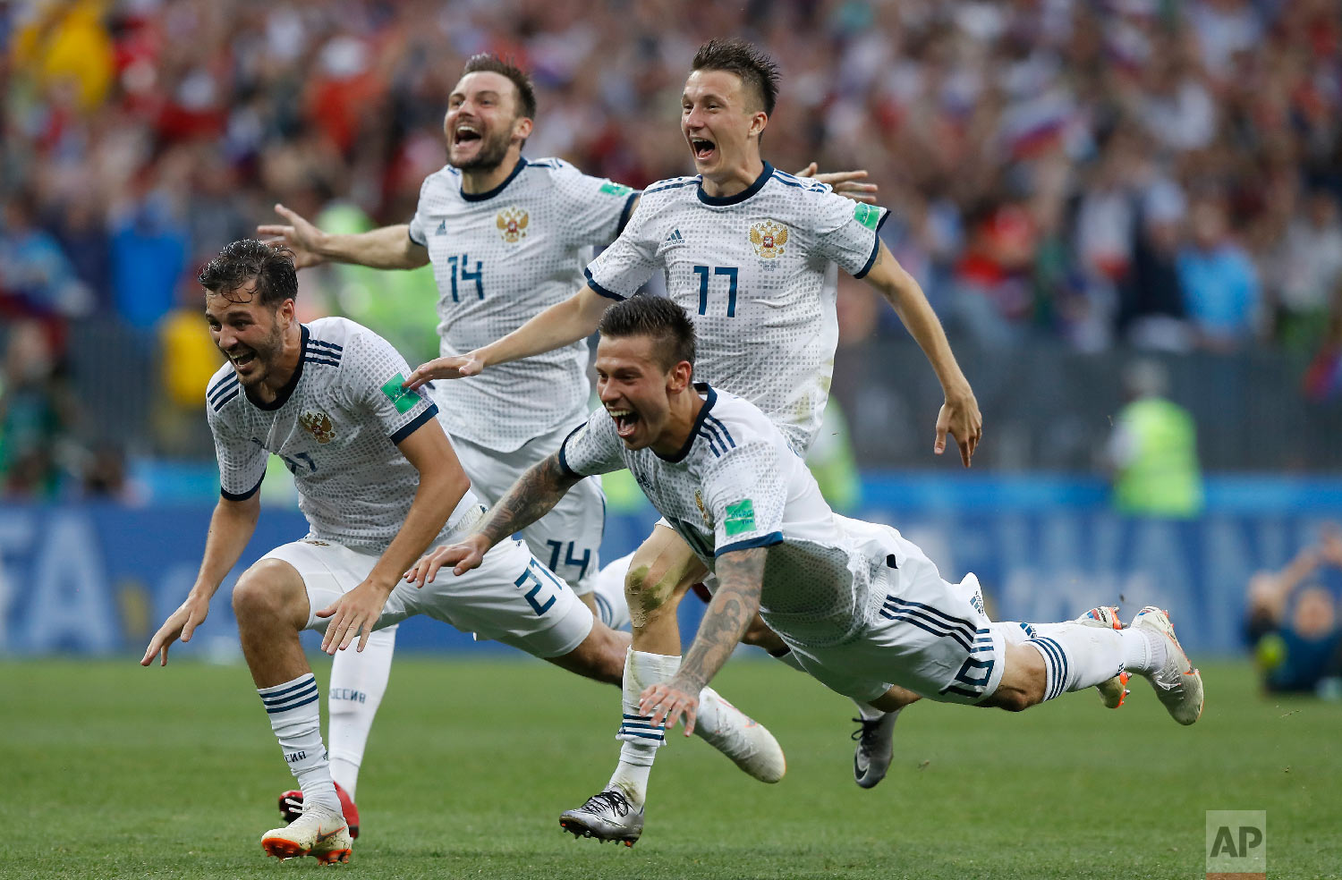 Russia's Fyodor Smolov, right, dives as he celebrates with teammates after Russia defeated Spain in a penalty shoot out during the round of 16 match between Spain and Russia at the 2018 soccer World Cup at the Luzhniki Stadium in Moscow, Russia, Sunday, July 1, 2018. (AP Photo/Manu Fernandez)