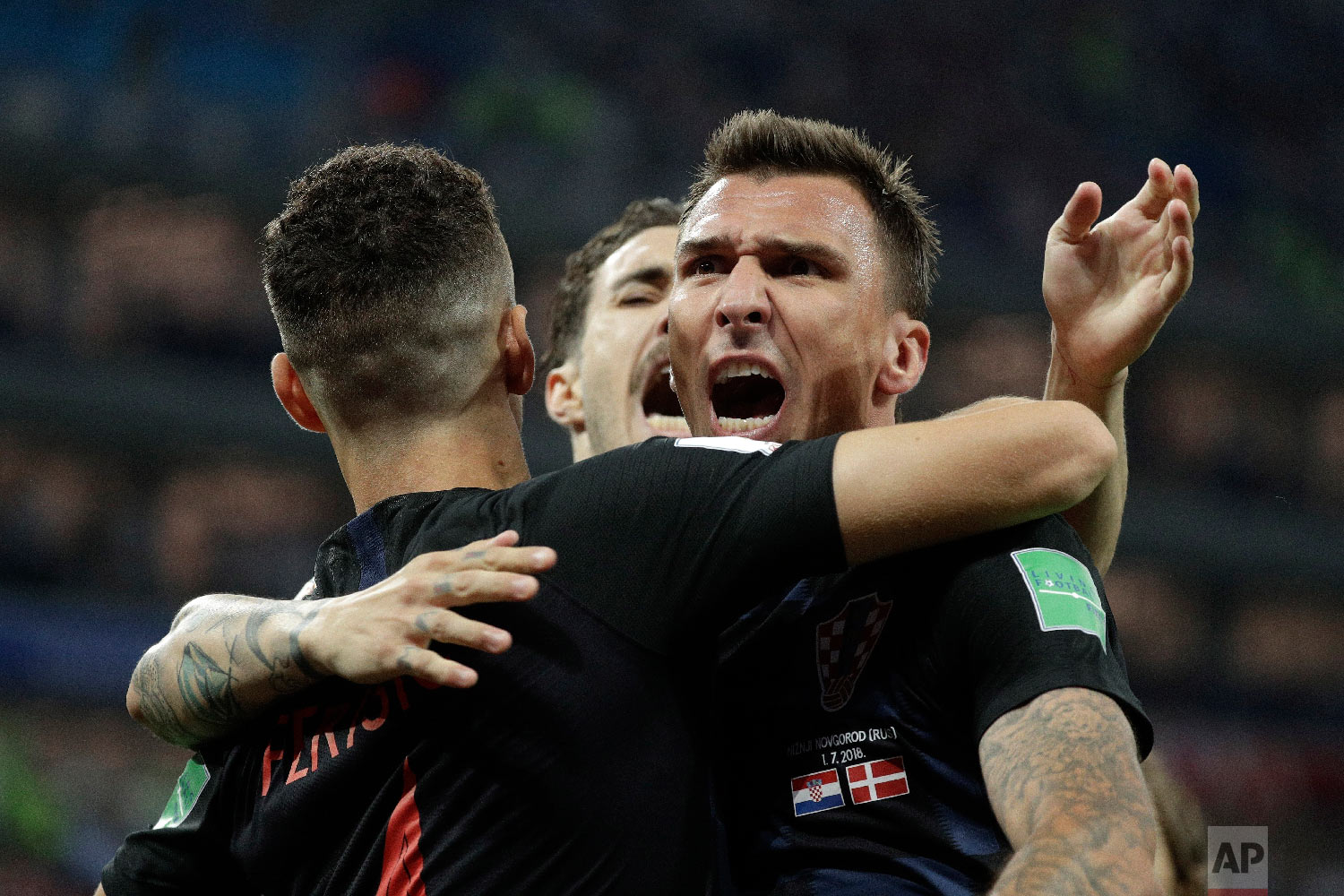 Croatia's Mario Mandzukic, right, celebrates with his teammates after scoring the opening goal of his team during the round of 16 match between Croatia and Denmark at the 2018 soccer World Cup in the Nizhny Novgorod Stadium, in Nizhny Novgorod, Russia, Saturday, July 1, 2018. (AP Photo/Gregorio Borgia)