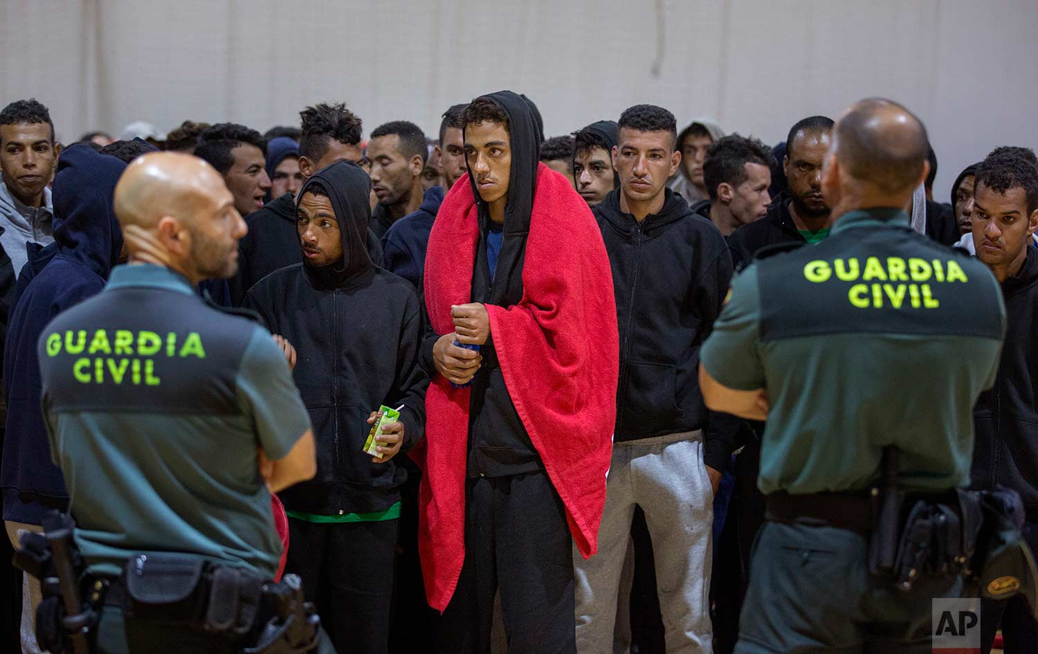 Guardia Civil officers stand guard as migrants gather at a makeshift emergency center for migrants at Barbate's municipal sports center, in the south of Spain, after being rescued by Spain's Maritime Rescue Service in the Strait of Gibraltar, Thursday, June 28, 2018. (AP Photo/Emilio Morenatti)