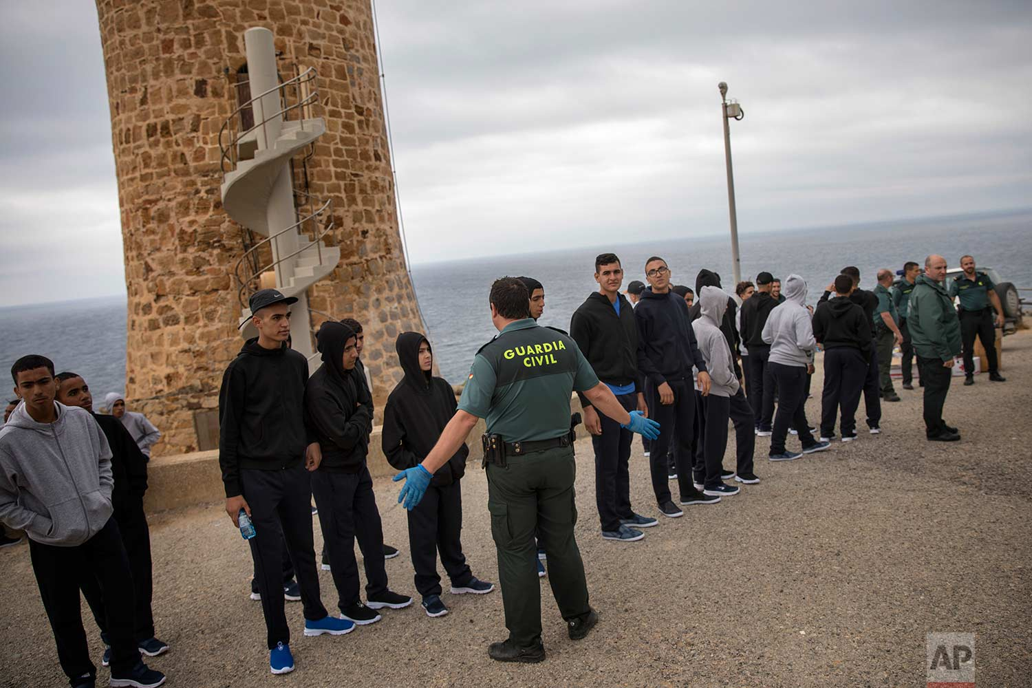 A Guardia Civil officer stands next to Moroccan migrants as they line up by the Camarinal Lighthouse after arriving on the beach by sailing in a rubber dinghy near Tarifa, in the south of Spain, Thursday, June 28, 2018. The group consisted of 35 unaccompanied Moroccan migrants. (AP Photo/Emilio Morenatti)