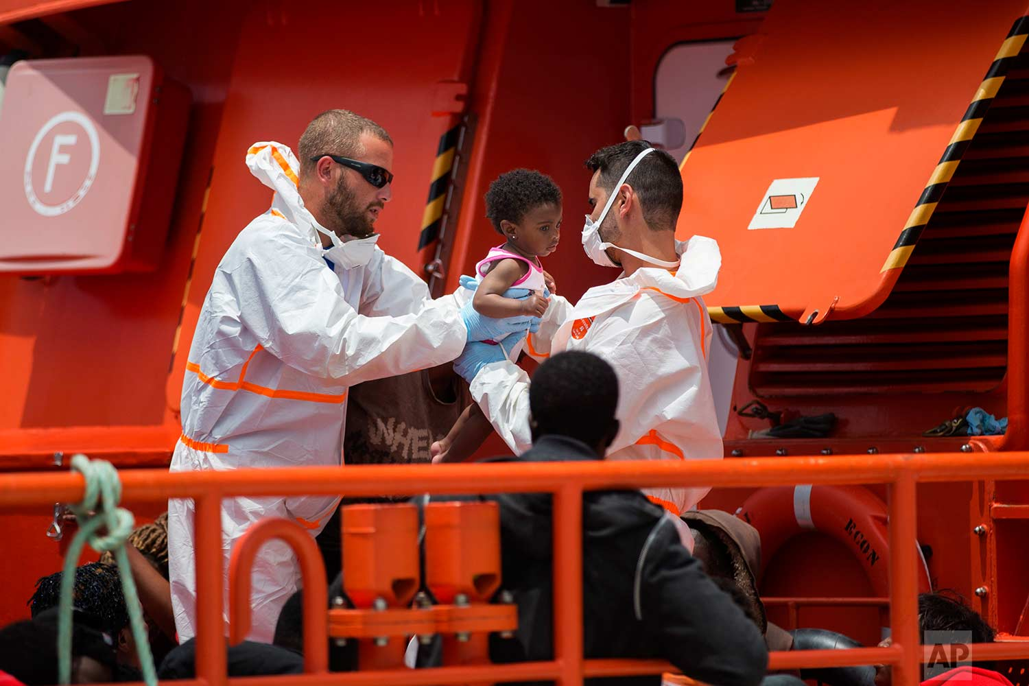 A baby is taken by rescue members at the port of Barbate, southern Spain, after being rescued by Spain's Maritime Rescue Service in the Strait of Gibraltar, Wednesday, June 27, 2018. (AP Photo/Emilio Morenatti)