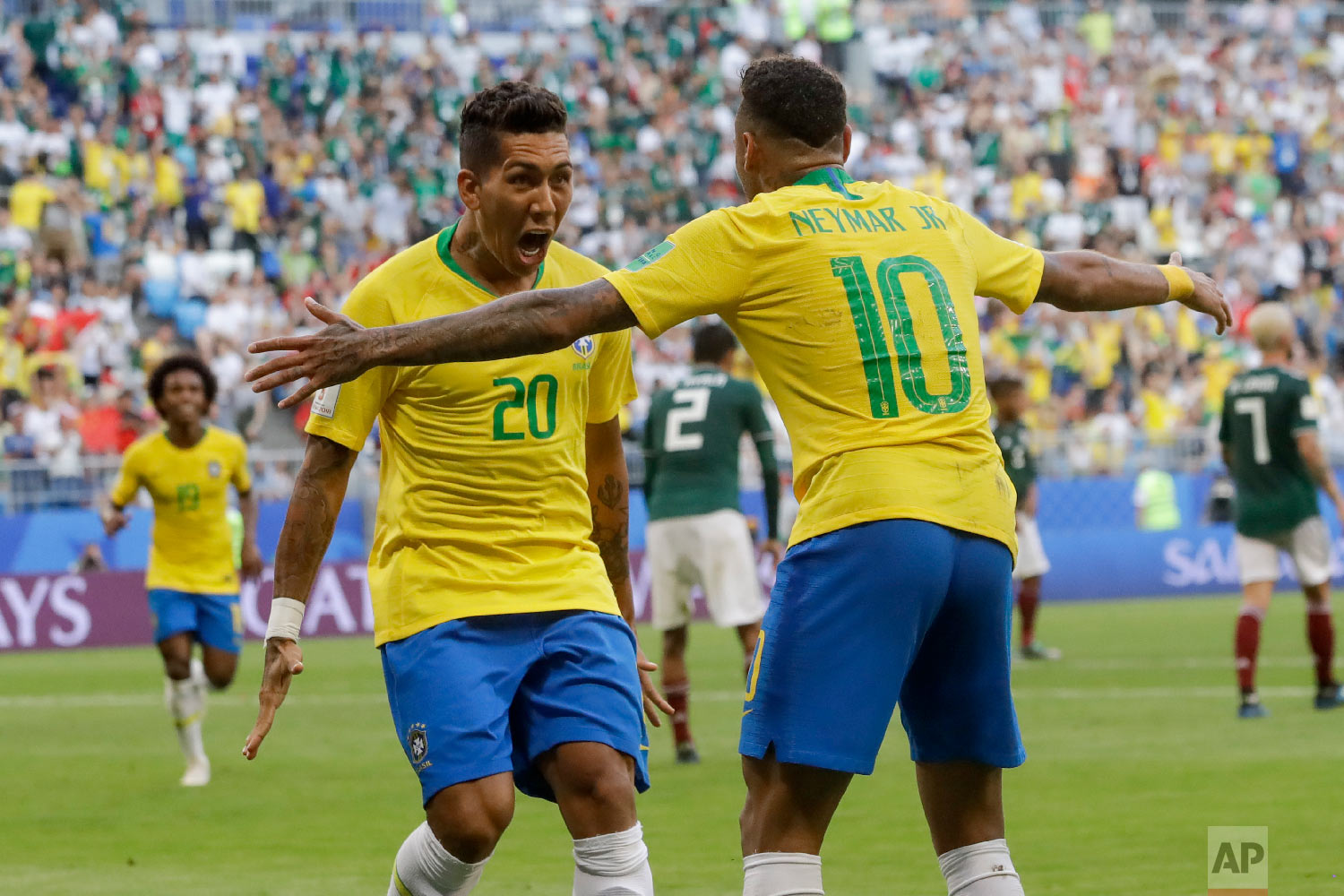 Brazil's Roberto Firmino, left, celebrates with Brazil's Neymar, right, after scoring his side's second goal during the round of 16 match between Brazil and Mexico at the 2018 soccer World Cup in the Samara Arena, in Samara, Russia, Monday, July 2, 2018. (AP Photo/Andre Penner)