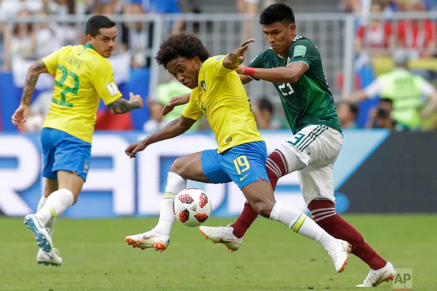 Mexico's Jesus Gallardo, right, vies for the ball with Brazil's Willian, center, during the round of 16 match between Brazil and Mexico at the 2018 soccer World Cup in the Samara Arena, in Samara, Russia, Monday, July 2, 2018. (AP Photo/Andre Penner)
