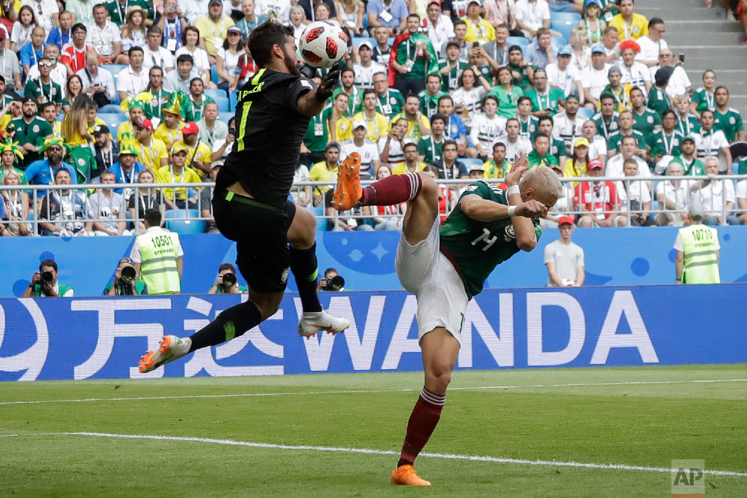 Brazil goalkeeper Alisson, left, blocks a kick by Mexico's Javier Hernandez, right, during the round of 16 match between Brazil and Mexico at the 2018 soccer World Cup in the Samara Arena, in Samara, Russia, Monday, July 2, 2018. (AP Photo/Andre Penner)